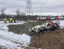 Firefighters at the scene of a crash Tuesday in which a cement truck ended up on its side iin the ditch near Highway 174 and Blair Road ERROL MCGIHON / POSTMEDIA