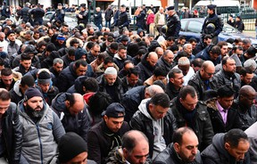 French riot police officers stand next to Muslims praying in the street during a protest in front of the city hall of Clichy, near Paris, on March 24, 2017, after an unauthorised place of worship was closed by local authorities. (AFP/PHOTO)
