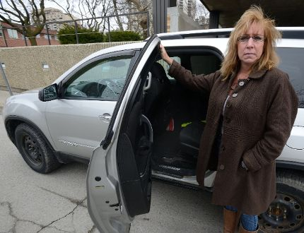 Sue Porter shows the backseat of her van, from which her daughter's laptop and some personal items were stolen. (MORRIS LAMONT, The London Free Press)
