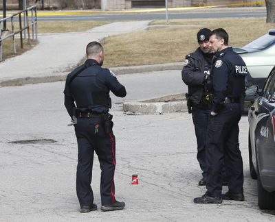 Police stand in driveway of 140 Adanac Dr. where a coffee cup is covering the shell casing after a vehicle was stopped by police leading to a foot pursuit to a nearby apartment where the officer's gun was discharged with no injuries on Wednesday March 29, 2017. (Michael Peake/Toronto Sun)