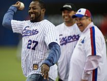 Former Montreal Expos slugger Vladimir Guerrero throws a ceremonisl pitch next to Montreal mayor Denis Coderre (right) and former teammate Orlando Cabrera during a pre-game ceremony as the Blue Jays face the Reds in MLB exhibition play in Montreal on April 3, 2015. (Paul Chiasson/The Canadian Press/Files)