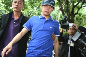 """In this Sept. 3, 2012, file photo, Vorayuth """"Boss"""" Yoovidhya, center, whose grandfather co-founded energy drink company Red Bull, is escorted by police in Bangkok, Thailand.(Thai Daily News via AP, File)"""