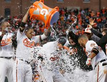 Baltimore Orioles' Mark Trumbo, centre, is doused with water by teammates as he runs crosses home plate after hitting a solo home run in the 11th inning against the Toronto Blue Jays in Baltimore, Monday, April 3, 2017. (AP Photo/Patrick Semansky)