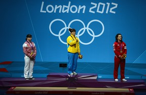 Maiya Maneza of Kazakhstan stands on the podium with the gold medal, Svetlana Tsarukaeva of Russia (L) the silver and Christine Girard of Canada (R) the bronze following the Women's 63kg Weightlifting final on Day 4 of the London 2012 Olympic Games at ExCeL on July 31, 2012 in London, England. (Laurence Griffiths/Getty Images)