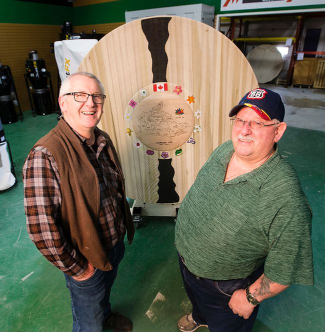 Members of Edmonton's Woodturners Guild, including Menno Klaassen, left, and Bill Nestor, other have created a large-scale commemorative platter in honour of Canada's 150th birthday. Its large size made it a very difficult piece to create. Greg Southam, Postmedia Network