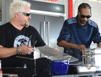 "This Feb. 26, 2017 photo made available by WorldRedEye.com, shows rapper Snoop Dogg, right, and Chef Guy Fieri, cooking together during a demonstration at the South Beach Wine & Food Festival in Miami Beach, Fla. Rappers Snoop, Action Bronson and Rev Run are ushering the culinary world into an era where shows like """"Martha and Snoop's Potluck Dinner Party"" are a hit and rappers like 2 Chainz drop cookbooks along with their albums. (Ryan Troy/WorldRedEye.com via AP)"