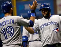 Kendrys Morales of the Toronto Blue Jays celebrates at home plate with teammate Jose Bautista after hitting a grand slam off of pitcher Blake Snell of the Tampa Bay Rays during a MLB game on April 6, 2017 at Tropicana Field. (Brian Blanco/Getty Images)