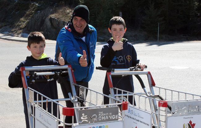 Caleb Marquis (left), Joe Roberts (centre) and Seth Marquis (right) give a thumbs-up before they head on their 3.8 kilometre walk from Canadian Tire to the OPP station while pushing shopping carts on Thursday. The brothers, also known as the Philanthro-Bros, donated the proceeds from colouring book sales to Roberts' campaign The Push for Change, which is raising awareness about youth homelessness. KATHLEEN CHARLEBOIS/DAILY MINER AND NEWS