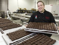 Marc Forrat holds a tray of chocolate-coated protein bars at his new factory in south London. Forrat's processing plant can turn out between 5,000 and 7,000 of the bars a week. (MIKE HENSEN, The London Free Press)