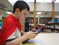 Madeleine Cummings, Edmonton Examiner AJ Clipperton, 9, uses Showbie on an iPad during his school's Dress as a Book Character Day last week. The app helps students store work and teachers give electronic feedback.