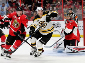 Senators defenceman Dion Phaneuf (left) tries to hold up David Pastrnak of the Bruins with goalie Craig Anderson looking on during Game 1 of their playoff series in Ottawa on Wednesday, April 12, 2017. (Wayne Cuddington/Postmedia)