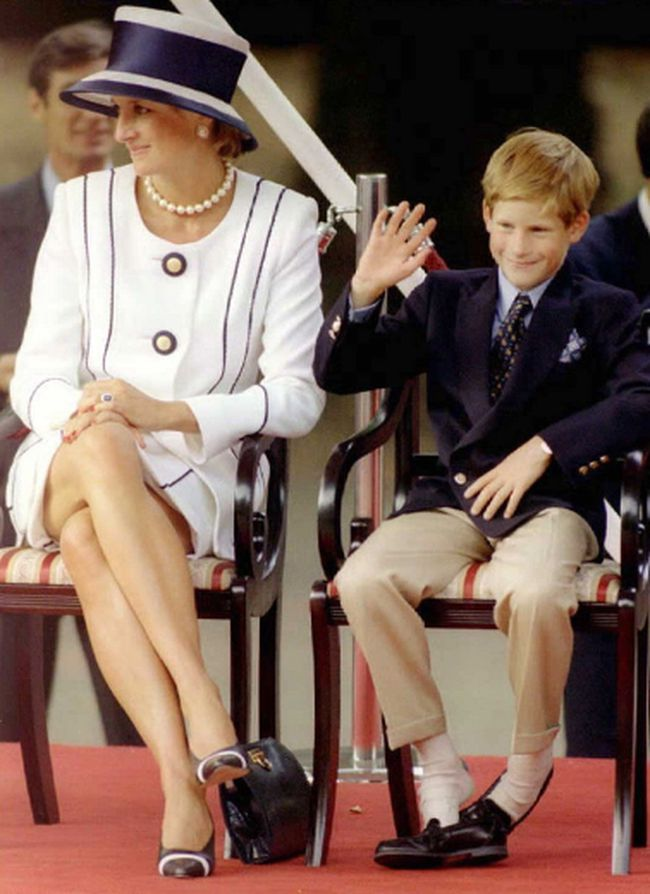 Princess Diana, left, and her son Harry watch veterans as they march past a dais on the Mall as part of the commemorations of VJ Day, August 19, 1995. The commemoration was held outside Buckingham Palace and was attended by 15,000 veterans and tens-of-thousands of spectators. (ALLAN LEWIS/AFP/Getty Images)