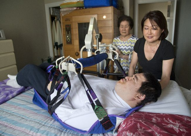 Alex Cha, 48, is lowered to his bed by his mom, Jeong Cha, 78, and guided by his sister, Jin Cha, at their north London condominium on Tuesday, April 11, 2017. (MIKE HENSEN, The London Free Press)