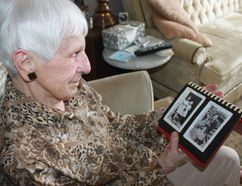 Marie Strapp, 90, of Grand Bend, looks at a photo she took of Geraldine Robertson at the former Mount Elgin Indian Industrial School in Muncey, Ont. Strapp, who worked at the residential school, recently reconnected with Robertson who is now an Aamjiwnaang First Nation elder who shares her story as a residential school survivor. Lynda Hillman-Rapley/Postmedia Network