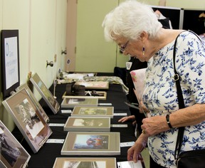 "Margaret Turner looks at photographs taken from the Queen's University archives at her first pop-up museum, ""Bring your Thing"" event on Tuesday. ""I immigrated to Canada 50 years ago from Ireland, I love to learn about the country's history,"" Turner said. (Taylor Bertelink/For The Whig-Standard)"