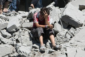A young Syrian boy cries as he sits on the rubble after a missile fired by Syrian government forces hit a residential area in the Maghayir district in the old quarter of the northern Syrian city of Aleppo in July 2015. (Postmedia Network)
