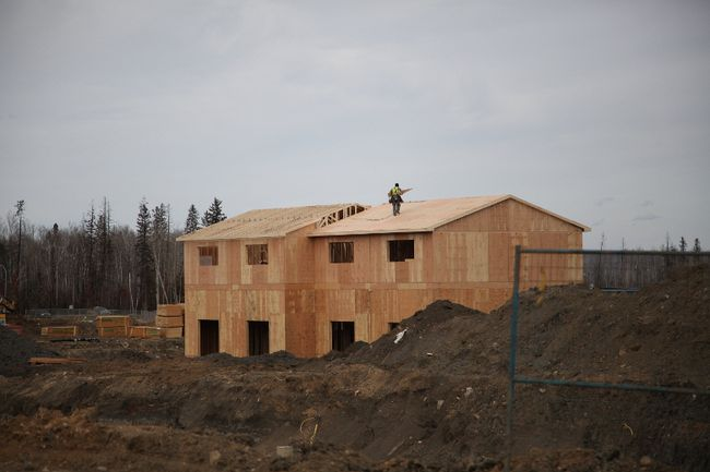 A construction worker carries building materials across the roof of a home being built in Fort McMurray, Alta.'s Abasand neighbourhood on Wednesday, April 5, 2017. Olivia Condon/ Fort McMurray Today/ Postmedia Network