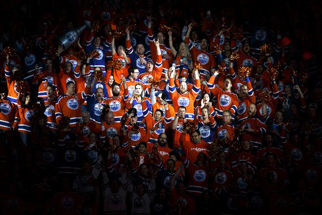 Holding the microphone high and proud, Park resident Robert Clark cheers with Oilers fans following the singing of the national anthem.