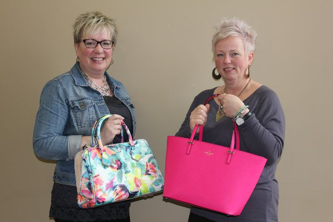 United Way's Lori Greer and Stephanie Lalonde display two of the items up for auction at the first Handbags for Heroes event, being held on Thursday.