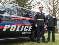 Bea Serdon/The Intelligencer Chief Ron Gignac of the Belleville Police Force and Captain Eric Rolfe of the Hastings and Prince Edward Regiment pose in front of the newly unveiled police cars that will have the support your troops yellow ribbon at the rear.