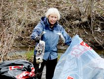 Karen Collett picks up one of the many bits of refuse she scooped out of the creek near Rotary Park during Saturday morning's Community-Wide Cleanup. (RONALD ZAJAC/The Recorder and Times)