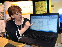 Tracey Peterson of Royal Homes shows a house plan she was working on at the Owen Sound Home and Cottage Expo Saturday. She and other home builders say the hot resale home market is sparking new construction. (Scott Dunn/The Sun Times, Owen Sound)
