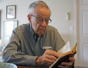 Bill Fitsell, at his home in Kingston on Saturday, reads the diary he wrote while serving in the Royal Canadian Navy during the Second World War. (Steph Crosier/The Whig-Standard)