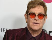 "In this March 25, 2017 file photo, Elton John arrives at Elton John's 70th Birthday and 50-Year Songwriting Partnership with Bernie Taupin celebration in Los Angeles. Elton John has cancelled more than a month of upcoming shows after contracting an ""unusual"" bacterial infection during a South America tour that left him in intensive care for two nights. The 70-year-old performer is expected to make a full recovery and hopes to return to a stage in Twickenham, England on June 3. (Photo by Jordan Strauss/Invision/AP, File)"