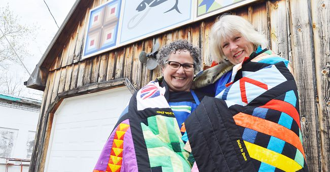 Denise Corneil, left, and Mary Simpson stand outside Corneil's house in Wardsville Ontario. They're draped in a collage of barn quilts, designs they picked out for a little project to commemorate Wardsville's bicentennial in 2010.