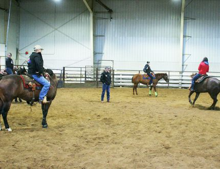 Locke Duce watches as one of the participants in his reining clinic in the J.E.Hawker Pavilion spins her horse around.