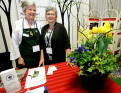 Sandy Wilson, president of the Garden Club of London, left, and club member Linda Hawker greet visitors at London's Home and Outdoor Show last week. (MORRIS LAMONT, The London Free Press)