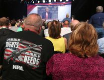 NRA attendees Bill and Karen Geittman watch a video of U.S. President Donald Trump while waiting for him to arrive for a keynote at the NRA-ILA Leadership Forum in Atlanta on Friday, April 28, 2017. (Curtis Compton/Atlanta Journal-Constitution via AP)