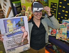 """Librarian Nadia Danyluk gets into the spirit of the upcoming Owen Sound Mini Comicon 2017 by displaying a """"Clark Kent mask"""" from the Superman comic Monday. The event celebrates comic books, graphic novels and video games Saturday in the Owen Sound & North Grey Union Public Library. (Scott Dunn/ The Sun Times, Owen Sound)"""