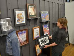 Artists' Co-op manager Morag Budgeon hangs some of the 70 pieces to be displayed in the Legacy Gallery until month's end. They're by high school artists from across Grey-Bruce. Awards to the juried winners will be presented Sunday. (Scott Dunn/The Sun Times, Owen Sound)