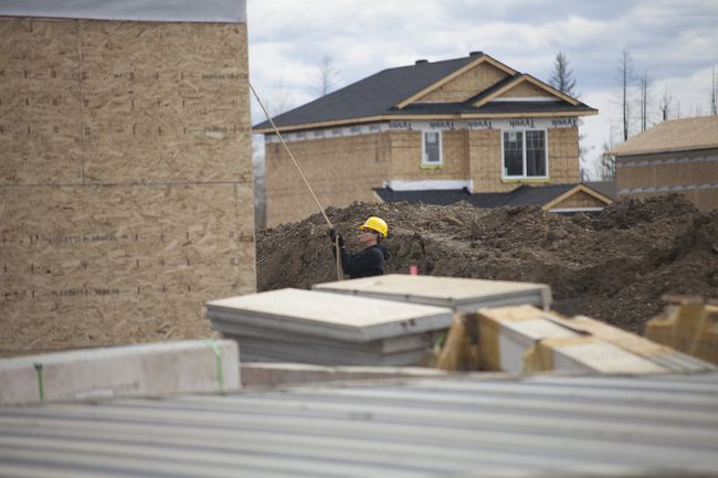 A construction worker helps with the completion of a house in the subdivision of Abasand Heights in Fort McMurray Alta. on Wednesday May 3, 2017. Robert Murray/Fort McMurray Today/Postmedia Network