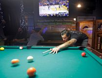 "In this Tuesday, May 2, 2017 photo, Dustin Smith, 28, plays pool as the Utah Jazz-Golden State Warriors NBA basketball playoff game is broadcast on a television at Poplar Street Pub in Salt Lake City. Salt Lake City leaders and tourism officials playfully jabbed back at Golden State Warriors players who bemoaned the lack of nightlife in Utah, hoping to combat the predominantly Mormon state's reputation as a boring place where it's tough to get a drink. The tourism agency in the state capital launched a new website and video Monday titled, ""There's nothing to do in Salt Lake"" that features people enjoying drinks and food at popular breweries, bars, restaurants and sporting venues. (AP Photo/Rick Bowmer)"