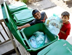 Eight-year-old Montessori Academy of London students Sagar Parekh (left) and William Sartori toss a bag of organic waste into a green bin at their school. After implementing a green bin program at the end of March, Montessori Academy officials estimate that the school has reduced the amount of trash it sends to the landfill by 80-85 per cent CHRIS MONTANINI\LONDONER\POSTMEDIA NETWORK