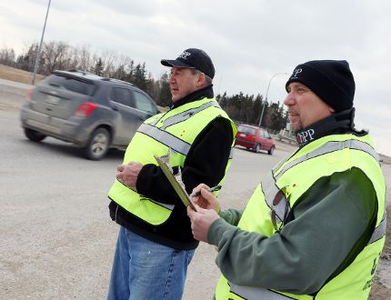 West St. Paul Citizen on Patrol Program coordinator Detlef Hindemith and a volunteer watch for and record the number of distracted drivers at the intersection of HIghway 8 and Grassmere Road.