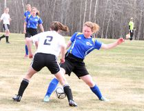 Haylee Creed of the St. Thomas Aquinas Saints women's soccer team attempts to get the ball past Rainy River Owls defender Paige Stamler when the teams met Monday, May 8 in Kenora in NorWOSSA 'A' action. The Saints won 5-0. SHERI LAMB/Daily Miner and News/Postmedia Network