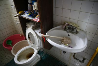 In this April 20, 2017, photo, underwear is wedged behind the faucet of the bathroom sink inside the home of suspected child webcam cybersex operator, David Timothy Deakin, from Peoria, Ill., during a raid in Mabalacat, Philippines. Children's underwear, toddler shoes, cameras, bondage cuffs, fetish ropes, meth pipes, stacks of hard drives and photo albums cluttered the stuffy, two-bedroom townhouse. In his computer files, there were videos and images of children engaged in sex acts. (AP Photo/Aaron Favila)