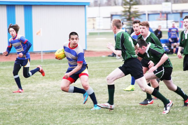 PAUL KRAJEWSKI HIGH RIVER TIMES/POSTMEDIA NETWORK. Luis Gomez, #17 Mustangs prop, dodges a tackle during a game against the Springbank Phoenix at Ècole Highwood High School in High River, Alta., on April 26. The 'Stangs won by 34-5.