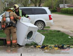 Winkler Fire Chief Richard Paetzold and a firefighter examine a dryer that was taken out of a local home after the contents burst into flames. Nobody was hurt, and damage was limited to the contents of the dryer. (GREG VANDERMEULEN/Winkler Times)