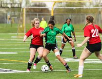 Kaitlin Swartz of the Lacombe Composite High School Rams battles with her H.J. Cody Lakers opponent for possession at MEGlobal Field on Tuesday afternoon. The Rams defeated the Lakers 3-2. (Ashli Barrett/Lacombe Globe)