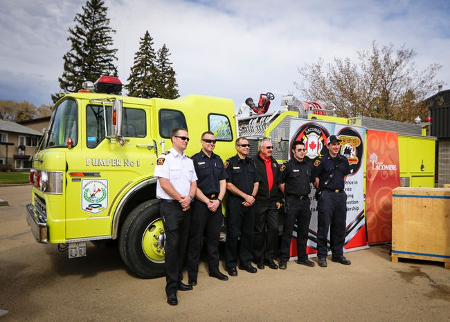 Deputy Fire Chief Drayton Bussiere, members of the Lacombe Fire Dept. and City of Lacombe Mayor Steve Christie (third from right) stand beside Engine One, which will be sent to Paraguay, Friday morning at the Lacombe Fire Hall. (Ashli Barrett/Lacombe Globe)