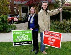 """Ian and Juliana McLean have two different signs to reflect their differing opinions on the city's proposed bus rapid transit system. The disagreement between the Thornton Avenue couple ratcheted up when Juliana came home and found the anti-BRT sign on their front lawn. """"I am a very progressive person,"""" she says. (Morris Lamont/London Free Press)"""