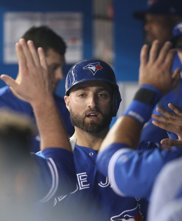 TORONTO, ON - MAY 11: Kevin Pillar #11 of the Toronto Blue Jays is congratulated by teammates in the dugout after scoring a run in the first inning during MLB game action against the Seattle Mariners at Rogers Centre on May 11, 2017 in Toronto, Canada. (Photo by Tom Szczerbowski/Getty Images)