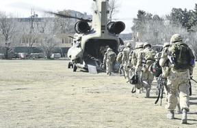 The last Canadians involved in the NATO training mission in Afghanistan board an American Chinook helicopter, on March 12, 2014, as they leave the International Security Assistance Force headquarters in Kabul, Afghanistan. (MCpl Patrick Blanchard/Canadian Forces Combat Camera file photo)