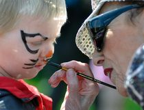 """Mitchell's Andrew Bauer, who turns three-years-old in a few weeks, gets the finishing touches put on his """"cat"""" face paint by Jennifer Black, of Goderich, during the 16th annual Mitchell Kinette Rubber Duck race held last Saturday, May 13 at Howie Morenz Memorial Gardens. ANDY BADER/MITCHELL ADVOCATE"""
