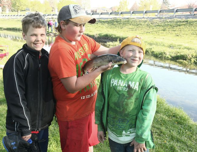 From the left, Ethan Govier, 10, smiles while Joey Clarke, 12, jokes with eight-year-old, Mick Clarke. The three caught a carp at the Seaforth Lions Annual Children's Trout Derby, however it was not legitimate for the tournament rules. (Shaun Gregory/Huron Expositor)