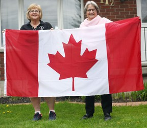 To the left, Maureen Agar and Lin Steffler showcase a Canadian flag last week in Seaforth. Both are part of the Huron East/ Seaforth Community Trust and they are excited to announce that each home owner from Seaforth are slated to receive a Canadian flag, which will be smaller than the one shown in the image. (Shaun Gregory/Huron Expositor)